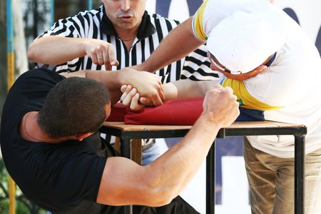 The referee has fixed a victory in a duel on armwrestling Stock Photo