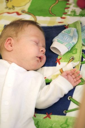 newborn baby easy sleeps on one side in a bed Stock Photo