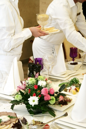 Waiters cover and serve a banquet table