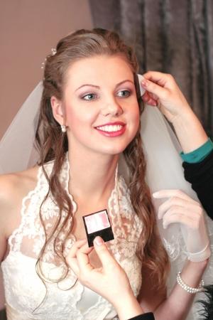 visagiste does a make-up to the bride before wedding