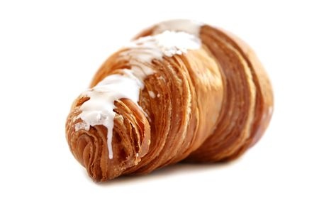 croissant with sugar glaze close-up on a white background