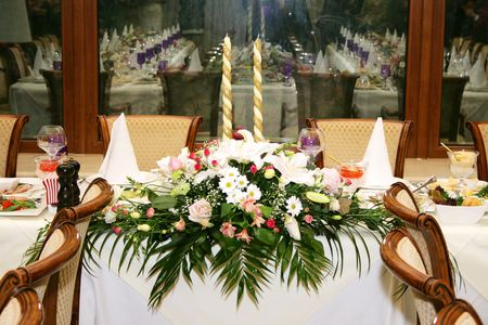 decoration work: The served celebratory wedding table decorated with flowers and candles