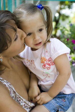 Mum kisses a daughter on a cheek
