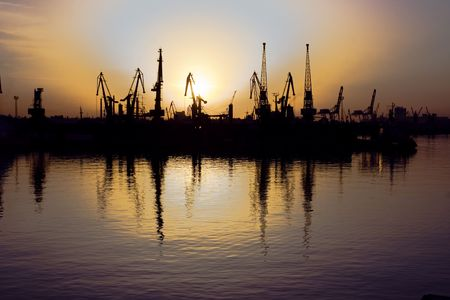 Black silhouettes of port cranes on trading moorings Stock Photo