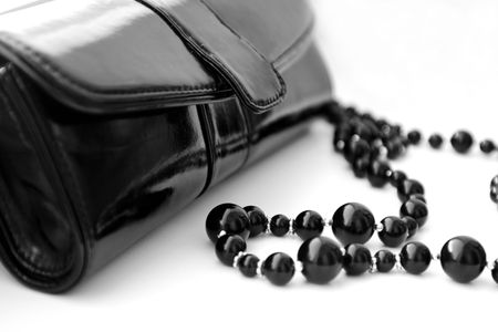 Black theatrical handbag and beads on a white background