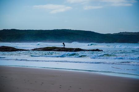 lonesomeness: Surf fisherman on a rock at One Mile Beach, Australia.