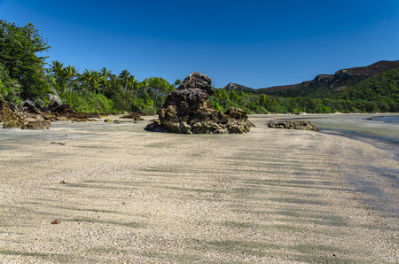 lonesomeness: A rock formation on a beach in tropical Queensland. Stock Photo