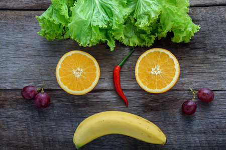 Vegetable sad face. Fresh organic Vegetables on Wooden table. Top view Stock Photo