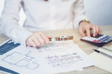 Businesswoman looking through a magnifying with calculator