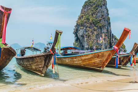 MAYA BAY, THAILAND - APRIL 14, 2014: Dramatic karst geography stands tall above traditional Thai longtail boats docked in the popular Maya Bay.