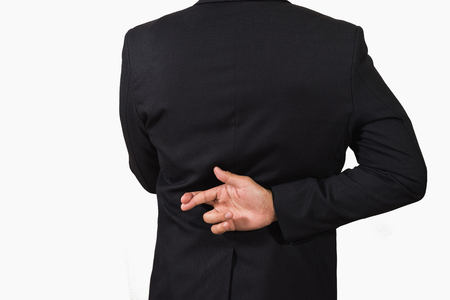 Empresario de traje oscuro con los dedos cruzados a la espalda