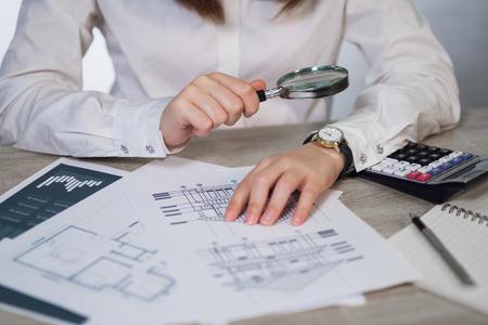 Imprenditrice guardando attraverso un ingrandimento sul tavolo