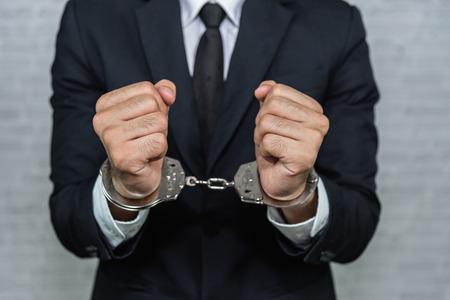 biznesmen w kajdankach aresztowany na białym tle na szarym tle