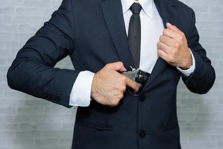 Businessman with gun sur fond gris Banque d'images