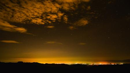 mily way on the city mountain night light Imagens