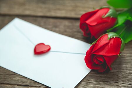 red rose flowers and letter on wood table