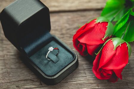 wedding ring and red rose flowers on wood table