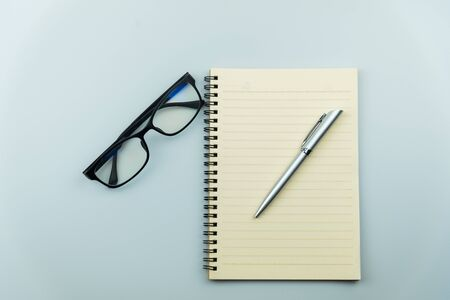 notebook, pen and glasses on gray background