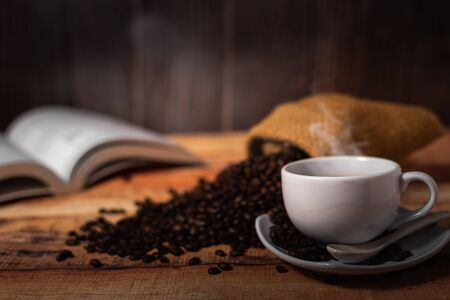 white cup of coffee and coffee beans on wood background