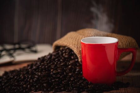 red cup of coffee with coffee beans on wood background 写真素材