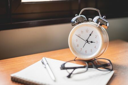 close up of glasses, clock and notebook on office table