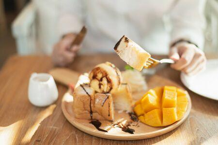 Close up of hand girl eating toast au miel sur table en bois dans le café Banque d'images
