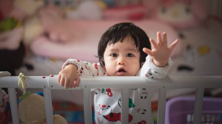 portrait of cute baby in child barrier