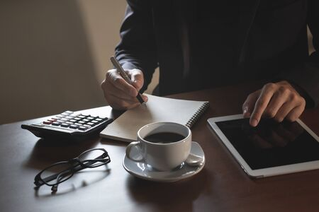 Business man working on digital tablet on wood table