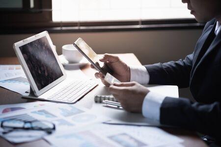 Uomo d'affari che utilizza il telefono cellulare e fa shopping con carta di credito