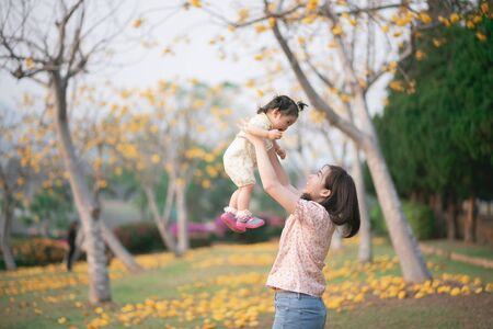 mother holding her cute baby girl in the flowers garden, Family concept