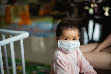baby wearing surgical mask stay at home. Covid-19 coronavirus concept