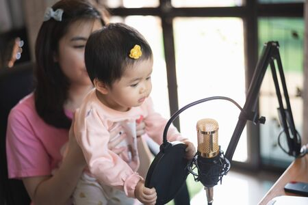 musician women and her daughter recording music at the music home studio