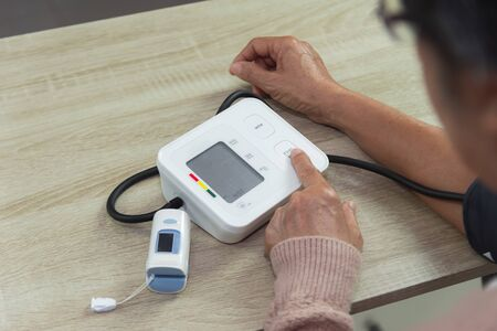 old woman with tonometer checking blood pressure level