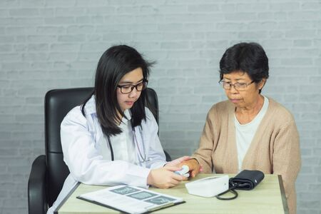 doctor checking pressure old woman on gray background Stock Photo