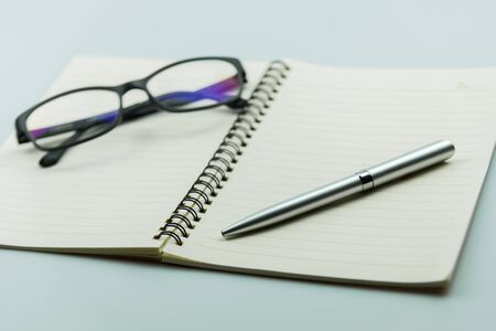 notebook, pen and glasses on white background