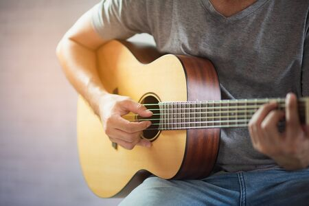 musician man playing acoustic guitar