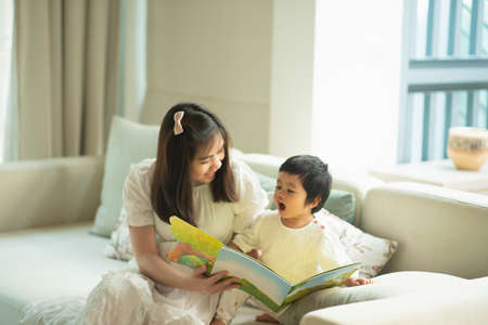 mother and daughter reading a book in the living room Stock Photo