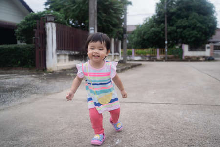 portrait of cute baby running on the road