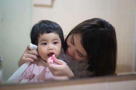 little girl brushing teeth with mom, family concept Standard-Bild
