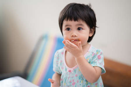 cute asian baby eating spaghetti in the dinning room