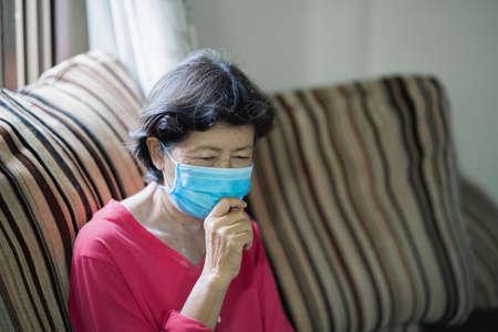 old women have a headache sitting on sofa