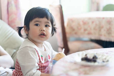 cute asian baby eating ice cream in the restaurant
