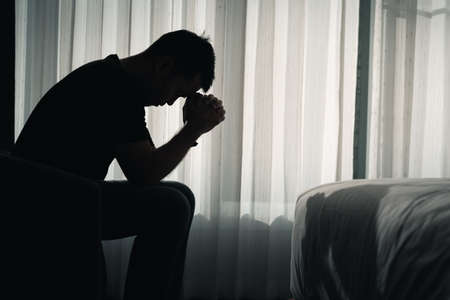 Silhouette depressed man sadly sitting on the bed in the bedroom, depression concept Stockfoto