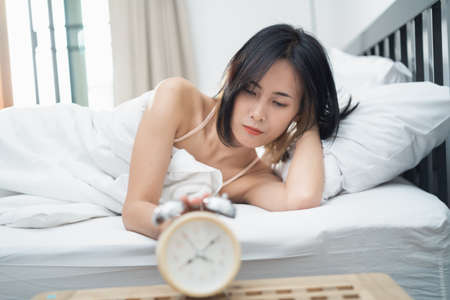 Woman short hair stretching in bed after wake up, back view