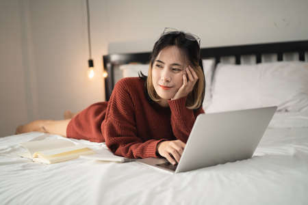 beautiful girl working with laptop on the bed, work from home concept