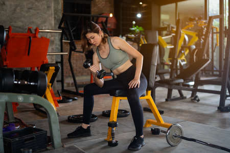 beautiful women exercise training with dumbbell in the gym, sport fitness concept Stock Photo