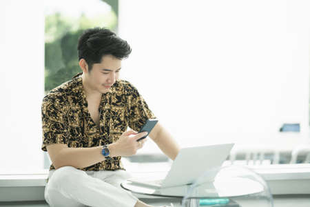 rich man using mobile phone and working with laptop at the cafe