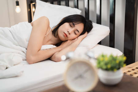 Young woman sleeping and alarm clock in the bedroom at home