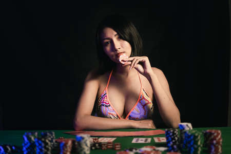sexy woman wearing bikini holding poker chips at the poker table in casino