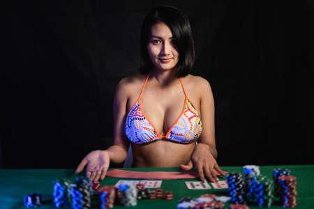 sexy woman wearing bikini playing poker at the casino